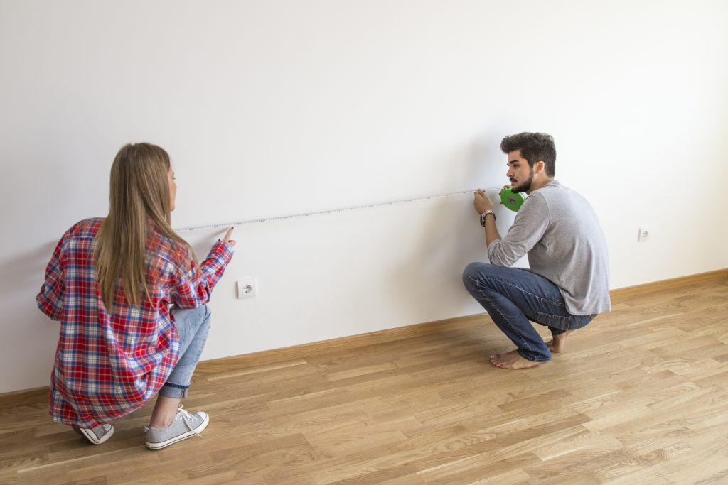 A couple is measuring a room.