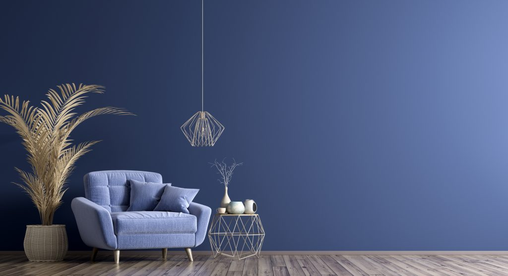 blue wall, grey laminate floor with blue chair, plant, wire lamp and table