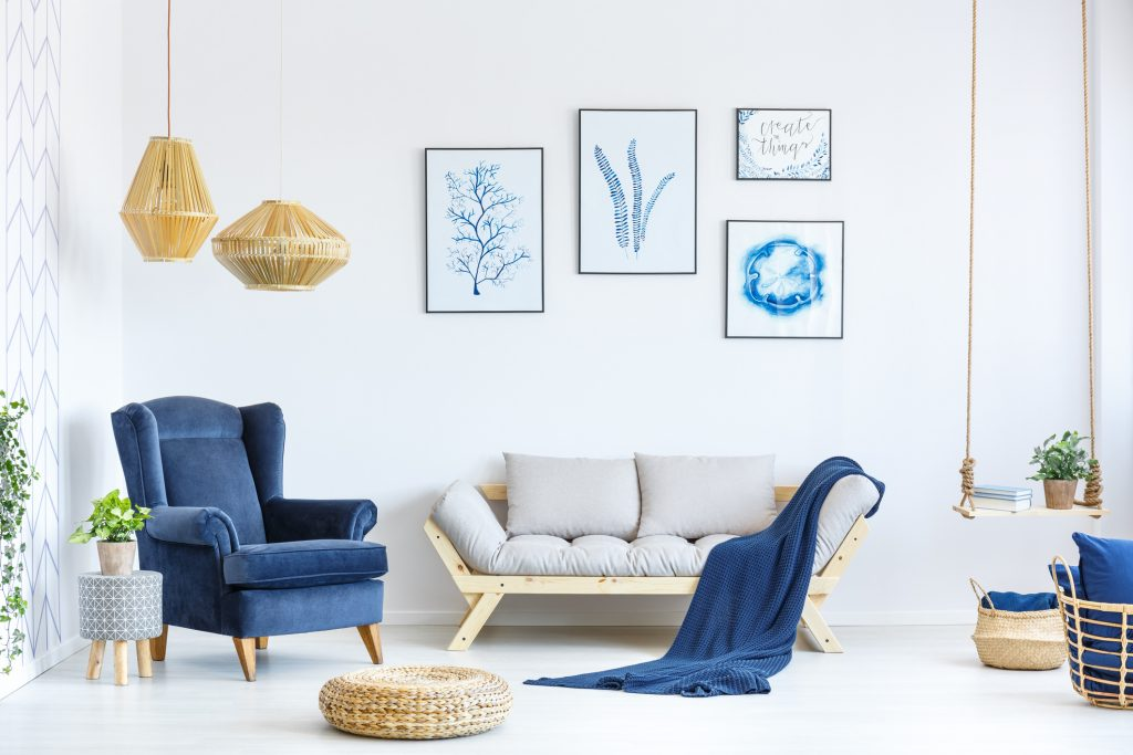 living room with blue blanket, blue chair and blue styled pictures.