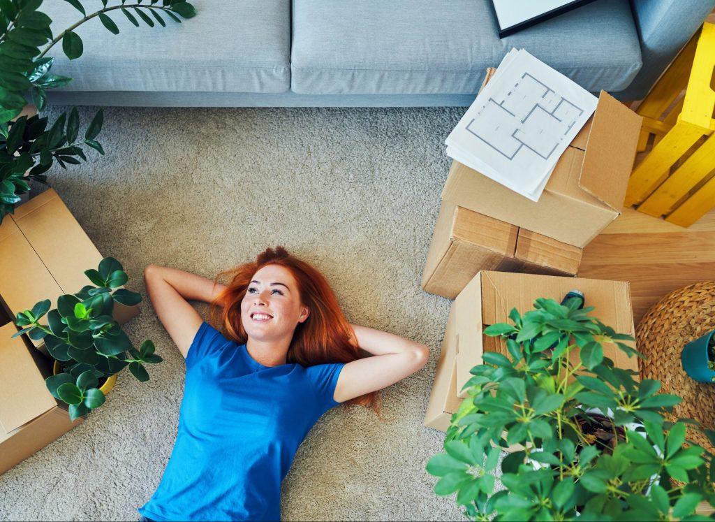 girl lying on new carpet in new home