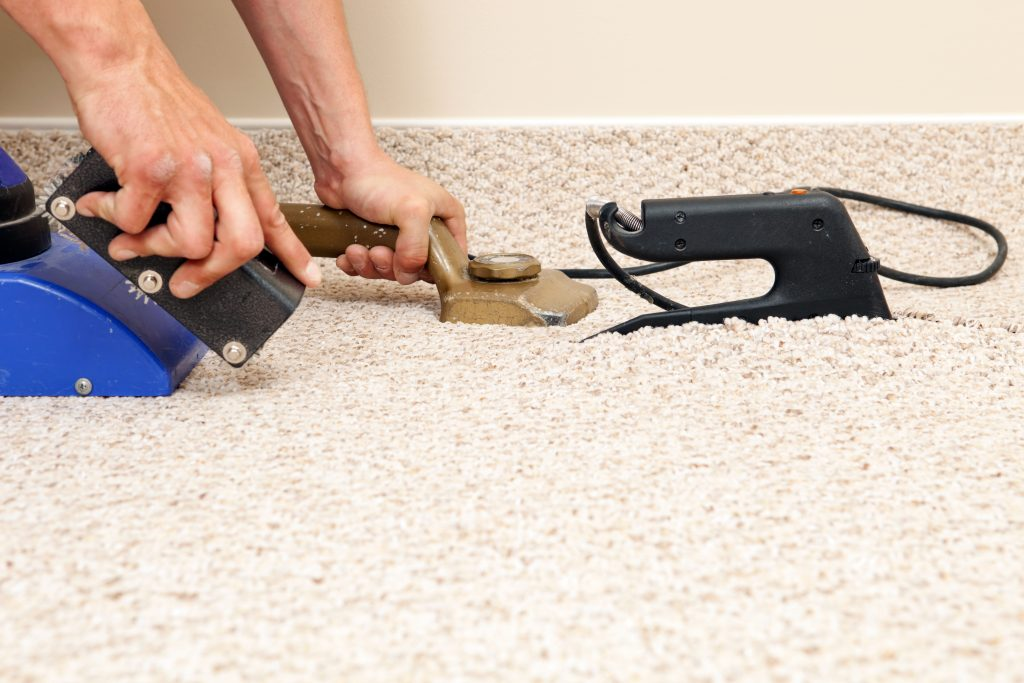 """A carpet installer is using a seam iron to join two sections of berber carpet in a bedroom at a house construction site. The left hand is holding a knee kicker carpet stretcher, and the right is operating a seam roller to hide the joint. The blue tool is a seam vacuum which extracts heat and pulls the seam tape up to the carpet. This image represents every component of the carpet seaming process."""