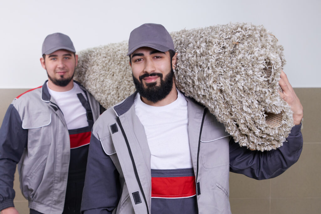 Carpet installers hauling in a roll of carpet