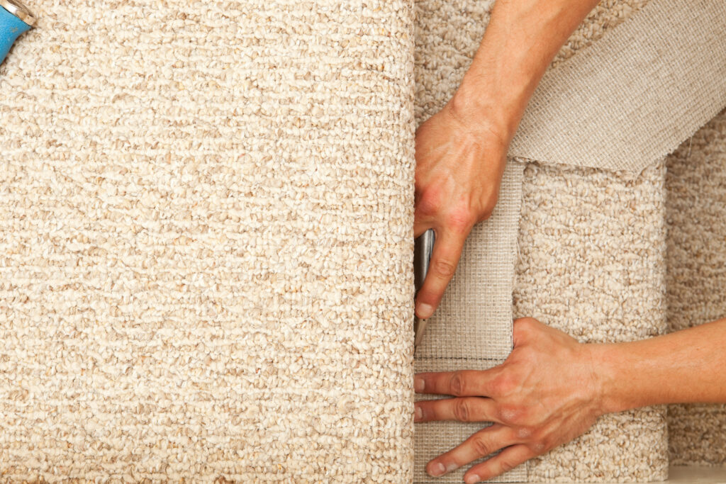 installer using a utility knife to trim new stair carpet for installation