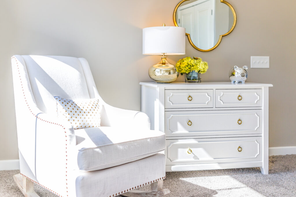 all white dresser and chair with light flooring and walls