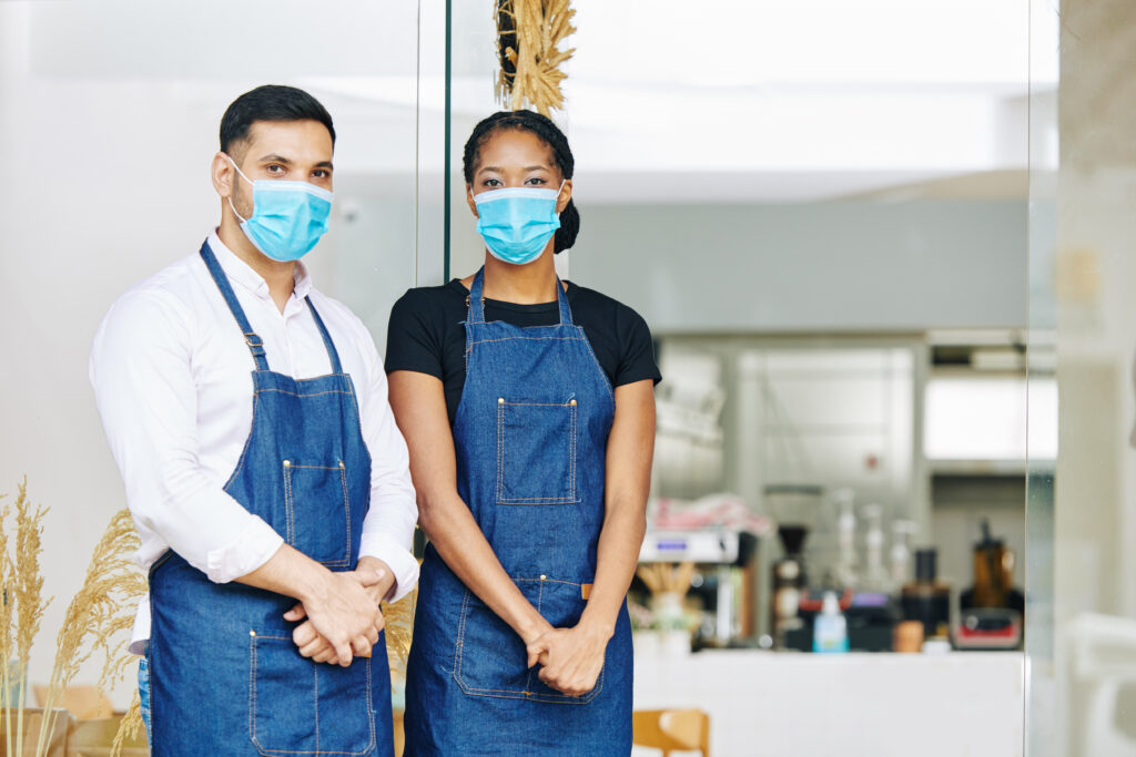 workers at a small local business wearing masks