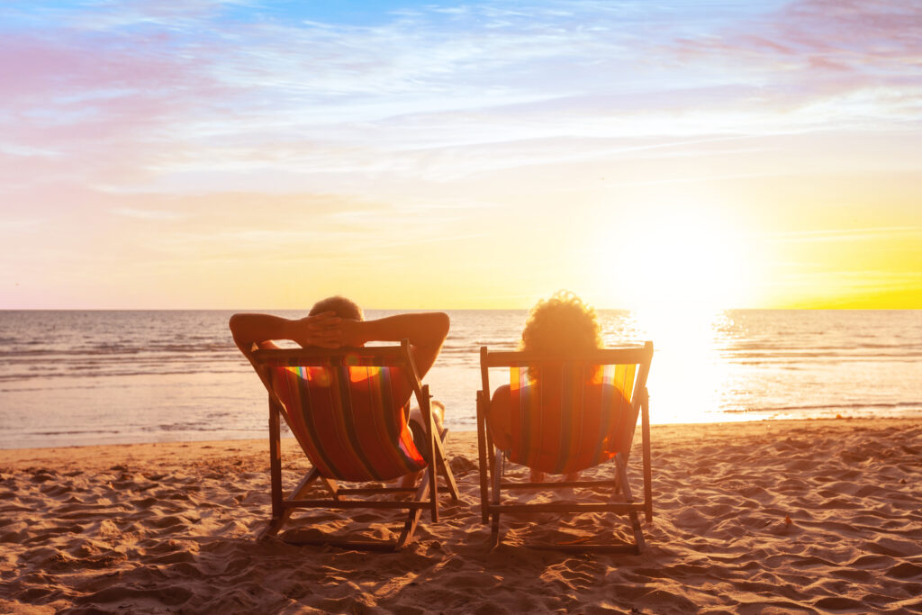 couple sitting in chairs on the beach watching the sun set