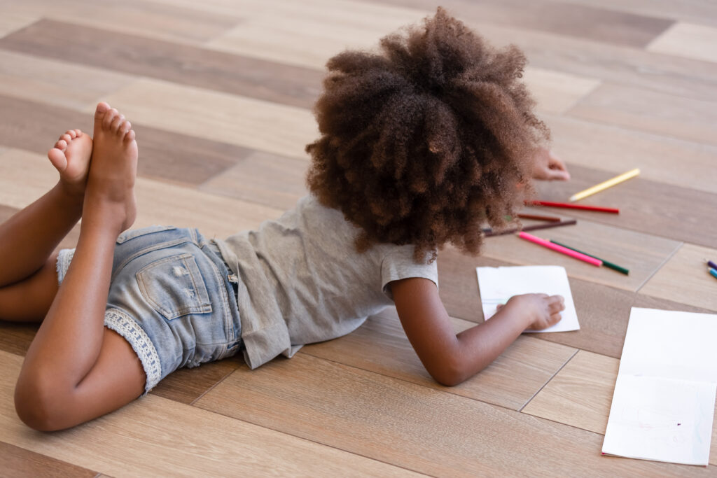 little girl on laminate floor coloring