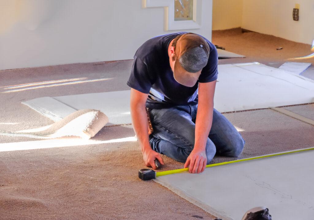 installer measuring carpet for installation